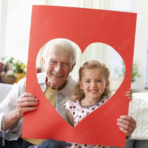 Caucasian grandfather and granddaughter looking through heart-shaped hole