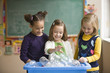 Students recycling plastic bottles in classroom