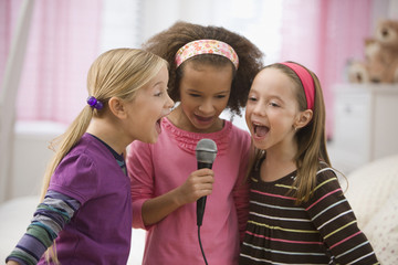 Girls singing into microphone together