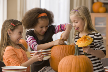 Girls carving pumpkins together