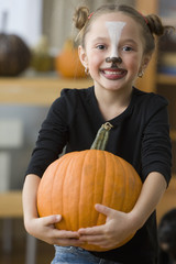 Caucasian girl in Halloween costume holding pumpkin