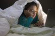Hispanic girl using laptop underneath covers