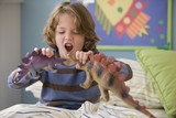 Caucasian boy playing with dinosaurs on bed
