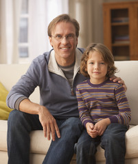 Caucasian man sitting on sofa with son