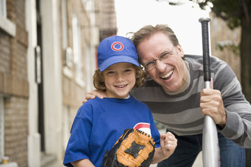 Caucasian father with son in baseball uniform