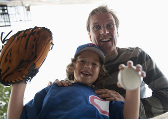 Caucasian boy in baseball uniform with father
