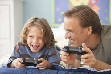 Caucasian father and son playing video game