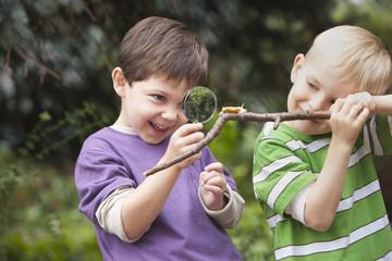 Caucasian boy looking at caterpillar on stick