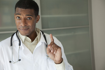 Black doctor in lab coat with hand raised