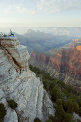 Caucasian woman practicing yoga on cliff near canyon