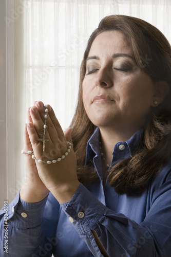 Hispanic woman holding rosary praying