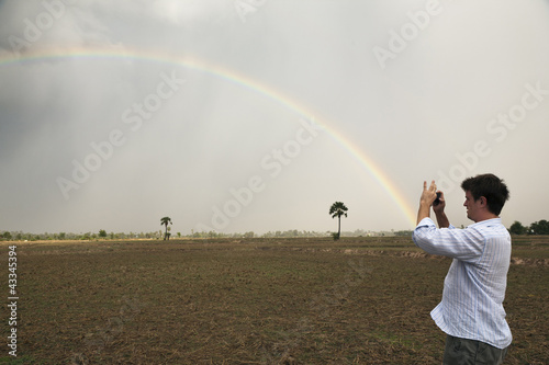 Man taking picture of rainbow