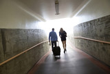 Couple walking with luggage in tunnel