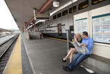 Couple sitting on train platform waiting for train