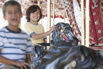 Excited brothers riding carousel