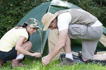 Hispanic couple setting up tent together