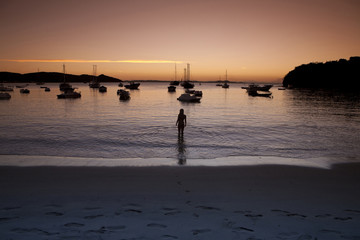 Young man wading in water at sunset
