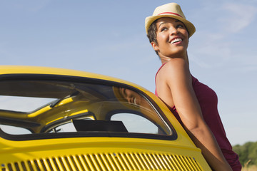 Smiling mixed race woman leaning on car