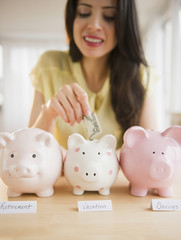 Mixed race woman putting money into piggy bank