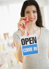 Mixed race woman holding shop open sign