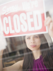 Mixed race woman putting up closed sign