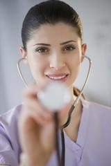 Mixed race nurse using stethoscope