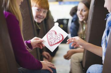 Girl giving friend Valentine on school bus