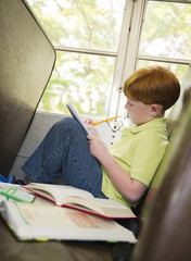 Caucasian boy doing homework on school bus