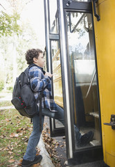 Mixed race boy getting onto school bus