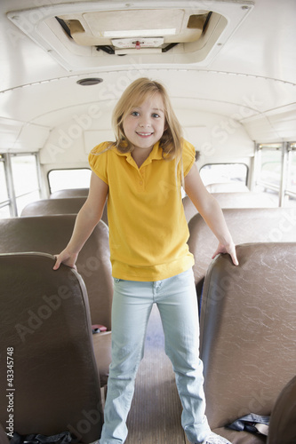 Caucasian girl riding school bus