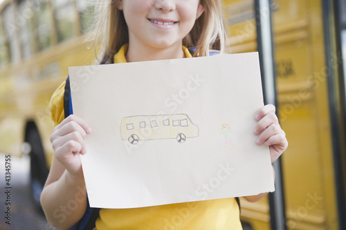 Caucasian girl holding drawing of school bus