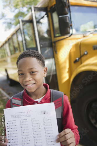 Mixed race boy holding test near school bus