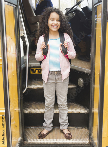 Hispanic girl getting onto school bus