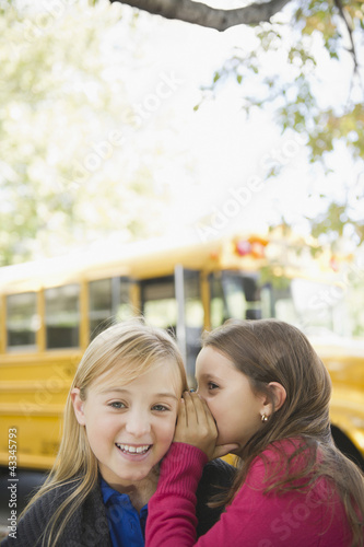 Caucasian girls whispering while waiting for school bus