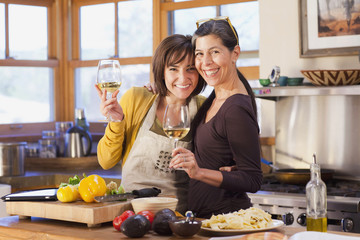 Hispanic friends cooking together in kitchen and drinking wine