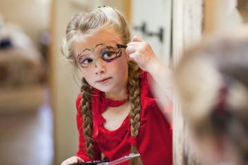 Caucasian girl putting on Halloween makeup