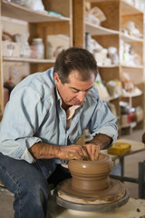 Caucasian man using pottery wheel