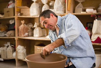 Caucasian man making pottery bowl