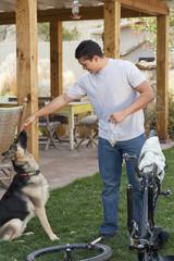 Hispanic man petting his dog