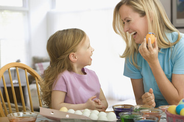 Caucasian mother decorating Easter eggs with daughter