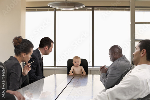 Business people looking at baby in conference room