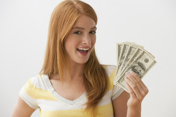 Caucasian teenage girl holding cash