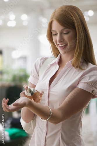 Caucasian teenage girl putting on perfume