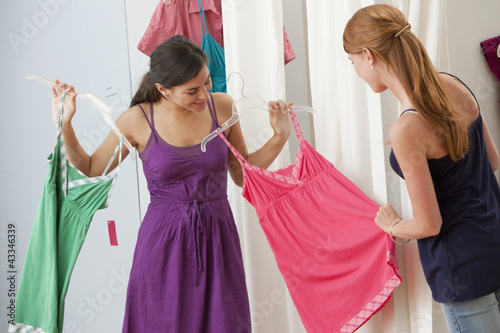 Caucasian girls shopping for dresses in shop