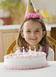 Caucasian girl sitting with birthday cake