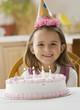 Caucasian girl sitting with birthday cake