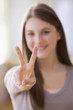 Caucasian teenage girl making peace sign