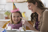 Caucasian mother putting cake icing on daughter's nose