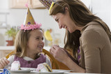 Caucasian mother and daughter eating birthday cake