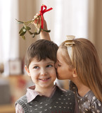 Girl kissing boy underneath mistletoe